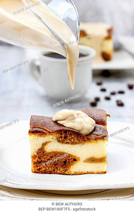 Pouring caramel sauce on piece of toffee and vanilla cake