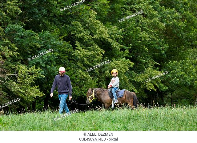 Father with daughter riding pony, Valle de Aran, Spain