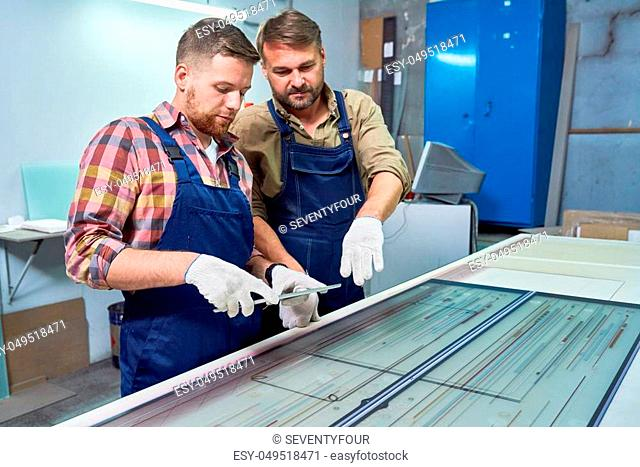 Portrait of two workers standing by laser engraving machine checking quality of operation, copy space