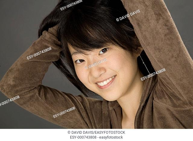 Portrait of a beautiful Asian teenager posing on a gray background with some attitude