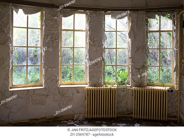 Room with windows and paint peeling of in abandoned house for the elderly people in holland