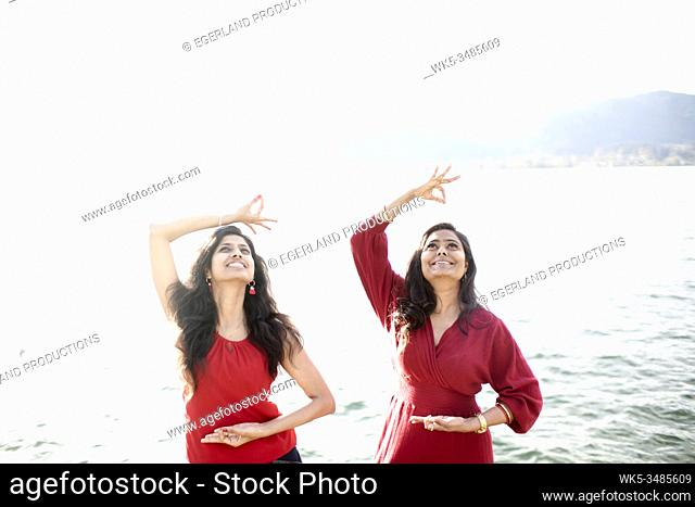 Two Indian women dancing by the lake. Tegernsee, Bavaria, Germany