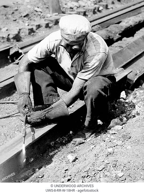 United States: c. 1935 A man working at dismantling railroad tracks by cutting them with a torch