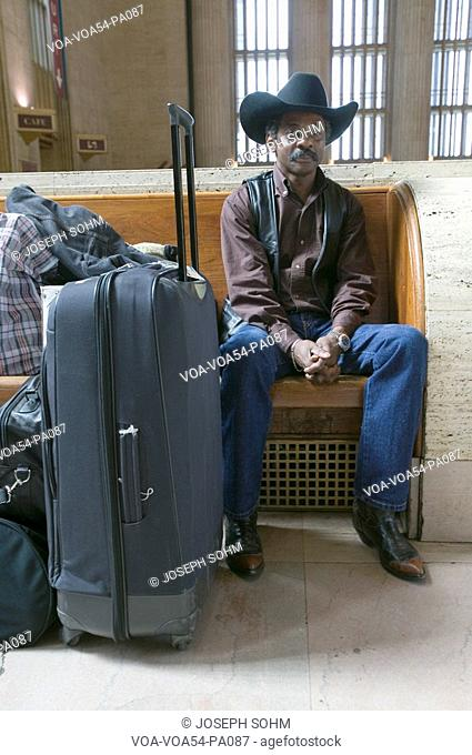 Black man with bags, cowboy hat and cowboy shoes waiting for train at 30th Street Station, AMTRAK Train Station in Philadelphia, PA