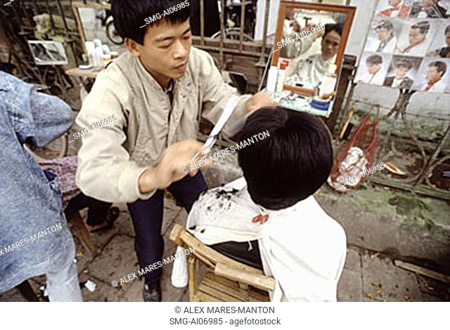 Vietnam, Hanoi, Barber cutting hair