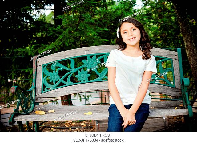 Picture of girl (6-7) sitting on bench