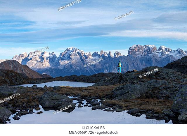 Hiker admire Brenta Dolomites near Black lake. Nembrone Valley, Adamello Brenta park, Trento province, Trentino Alto Adige, Italy, Europe