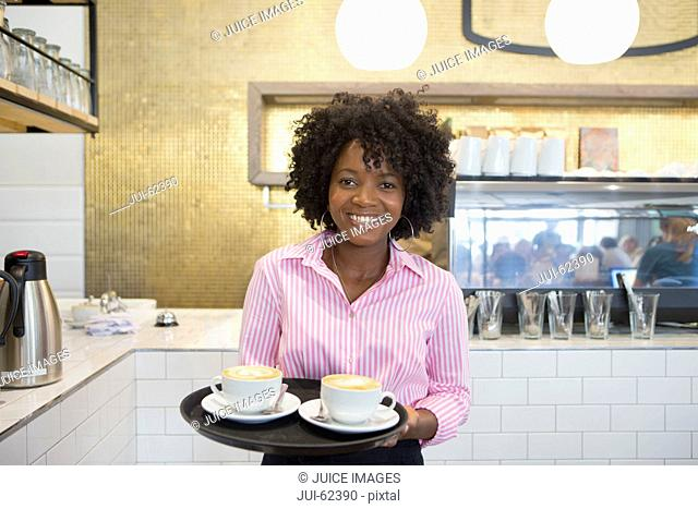 Smiling waitress holding tray of coffee in coffee shop