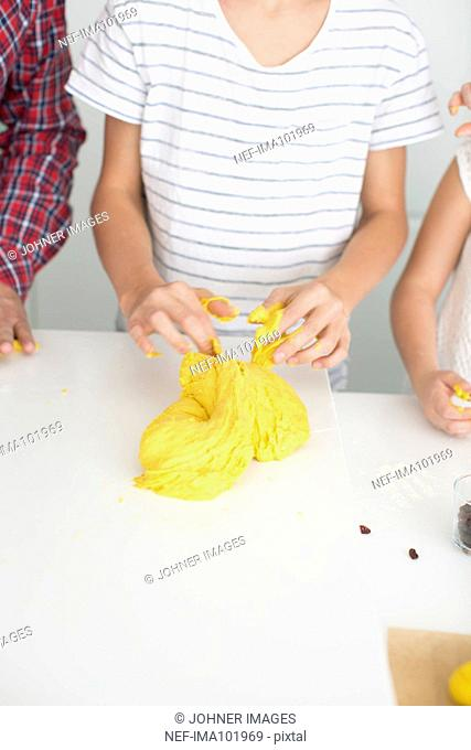Boy with father and sister preparing dough for saffron rolls