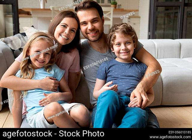 Portrait of happy full bonding family of four, sitting at warm wooden heated floor in living room at home. Smiling lovely young parents hugging little cute...