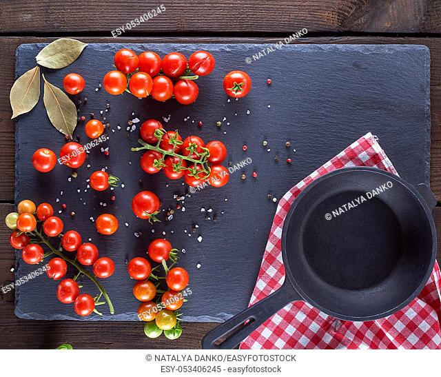 cast iron round frying pan and ripe red cherry tomatoes on a brown wooden table, close up