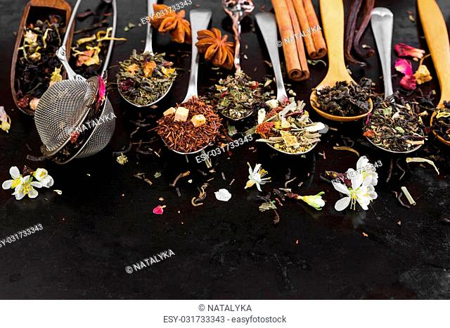 Aromatic flower tea in spoon on rustic black background