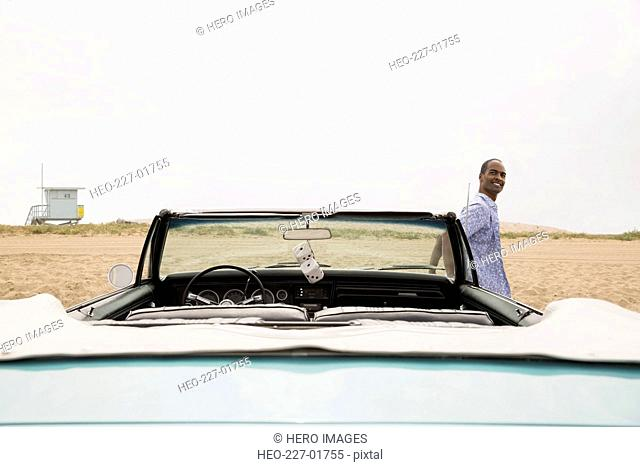 Man leaning on convertible at beach