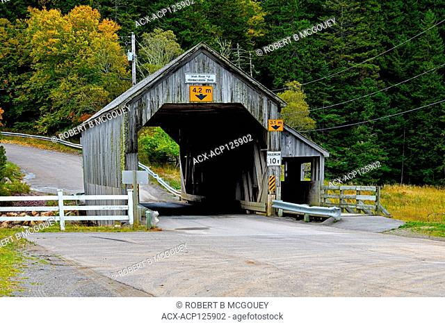A horizontal landscape image of the Hardscrabble covered bridge spanning the Irish River at Saint Martins, New Brunswick, Canada