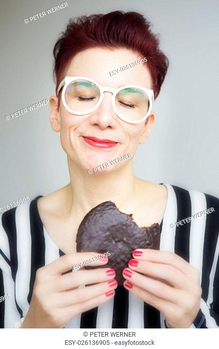 red-haired woman with big white glasses eating a big chocolate cookie