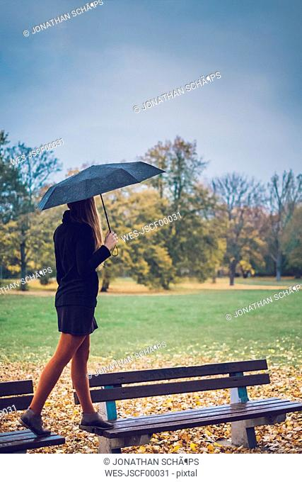 Young woman with umbrella balancing on two benches in autumnal park