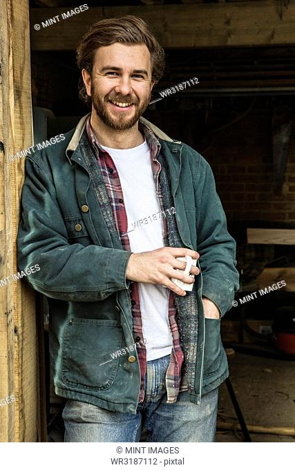 Bearded man standing in doorway of woodworking workshop, holding mug, smiling at camera