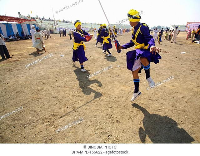 Young Nihangs or Sikh warriors performing swords stunts during the cultural events held for celebrations of 300th year of consecration of perpetual Guru Granth...