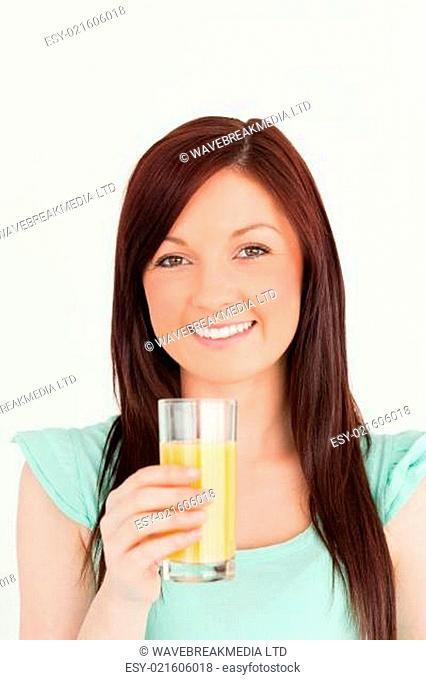 Cheerful red-haired woman enjoying a glass of orange juice in the kitchen