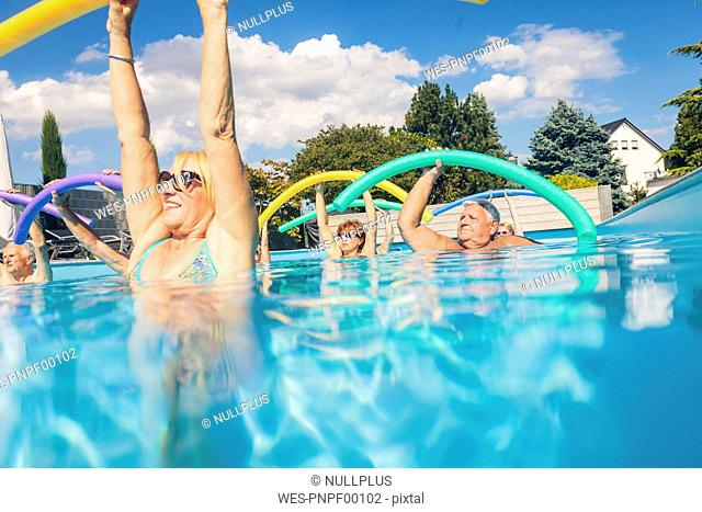 Group of seniors doing water gymnastics in pool