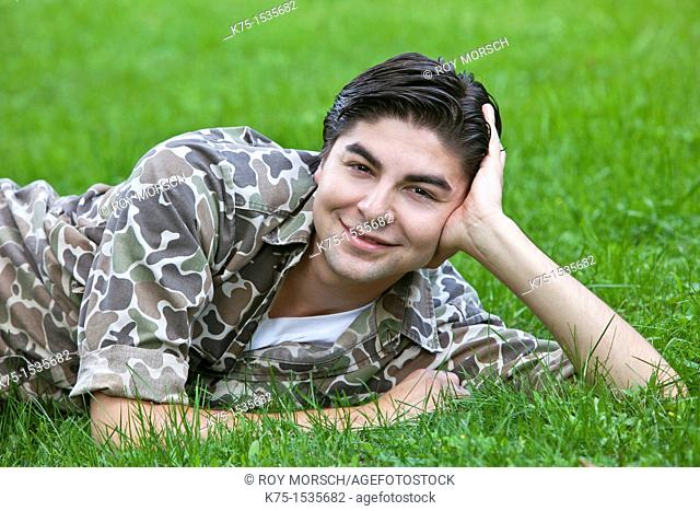 Young man lying in grass smiling for portrait