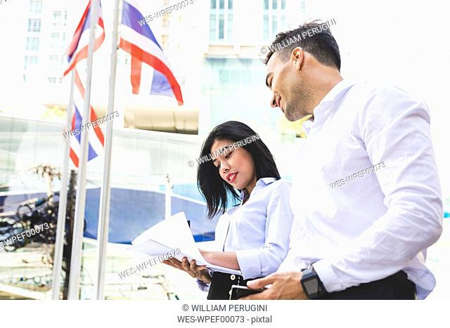 Thailand, Bangkok, businessman and businesswoman in the city looking at documents