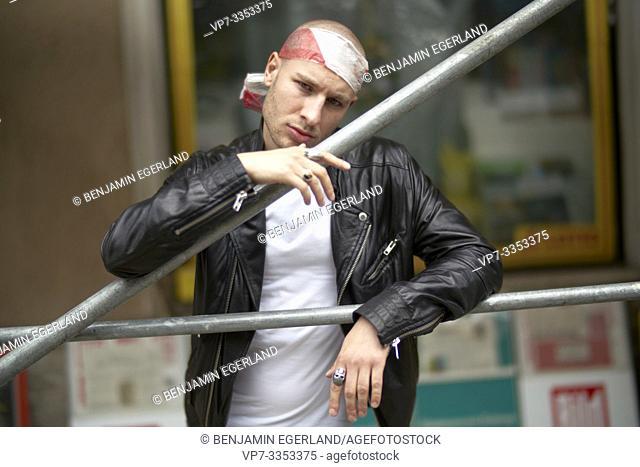 man in city, wearing barrier tape as bandeau