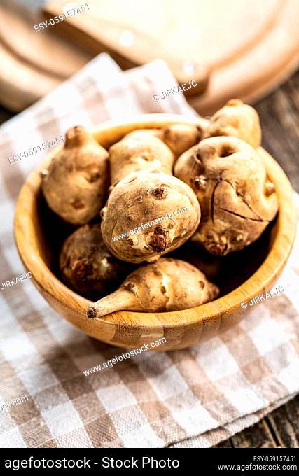 Raw jerusalem artichoke. Topinambur vegetable root in wooden bowl
