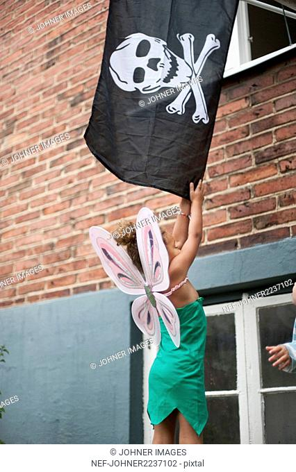 Girl in costume holding pirate flag