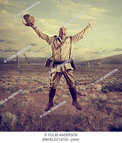 Hunter cheering in remote savanna landscape