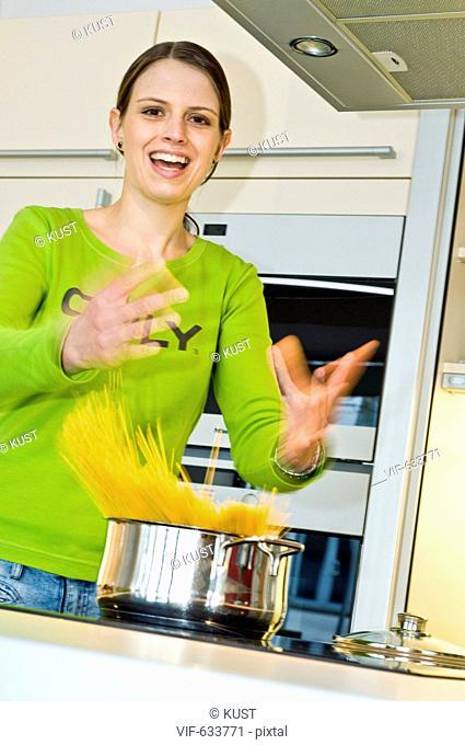 junge Frau wirft Spaghetti in Kochtopf - Nieder÷sterreich, Ísterreich, 14/02/2008
