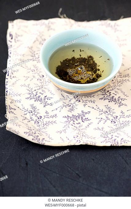Bowl of Earl Grey tea mixed with cornflowers on patterned cloth
