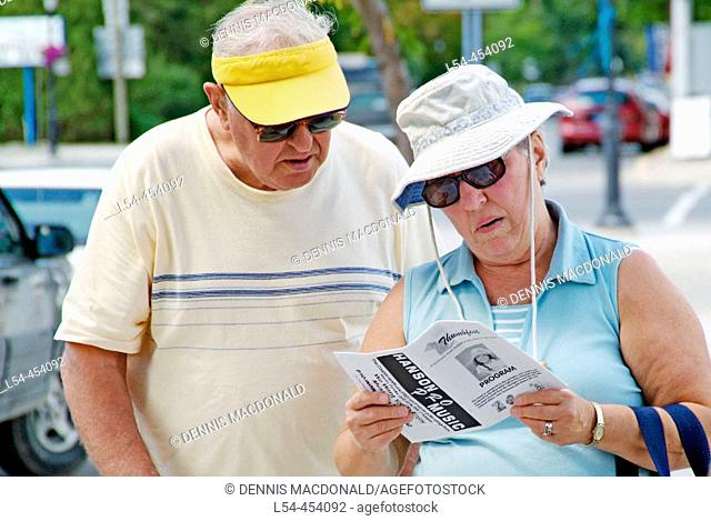 Senior citizen husband and wife look a sheet of directions and map to find their way