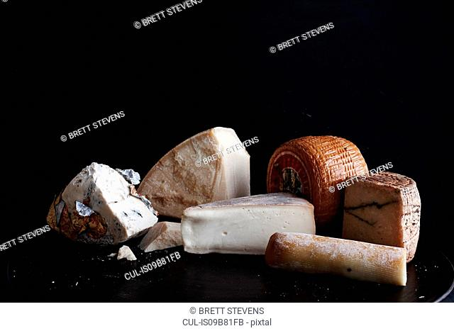Selection of cheese on black plate against black background, close-up