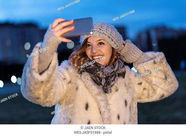 Laughing young woman taking selfie with smartphone at evening twilight