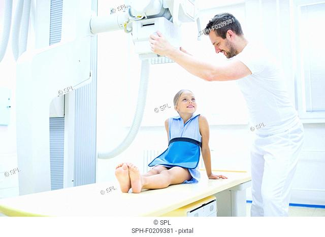 Doctor preparing girl for x-ray in hospital