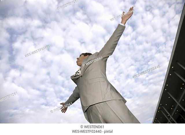 Businessman against cloudy sky, arms out, low angle view