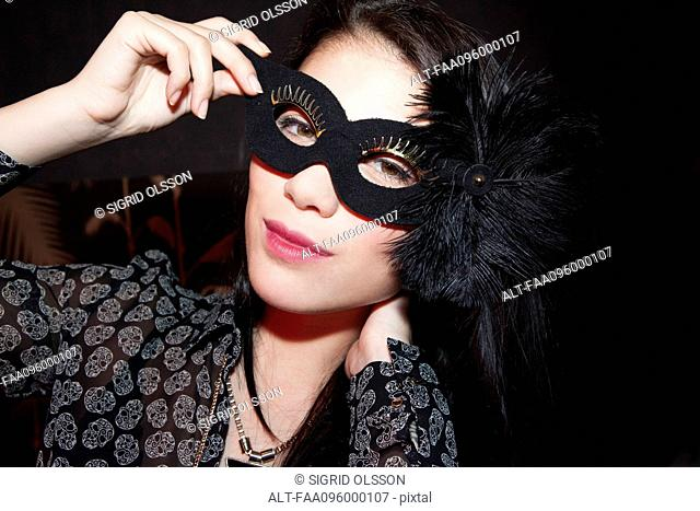 Woman wearing party mask, portrait
