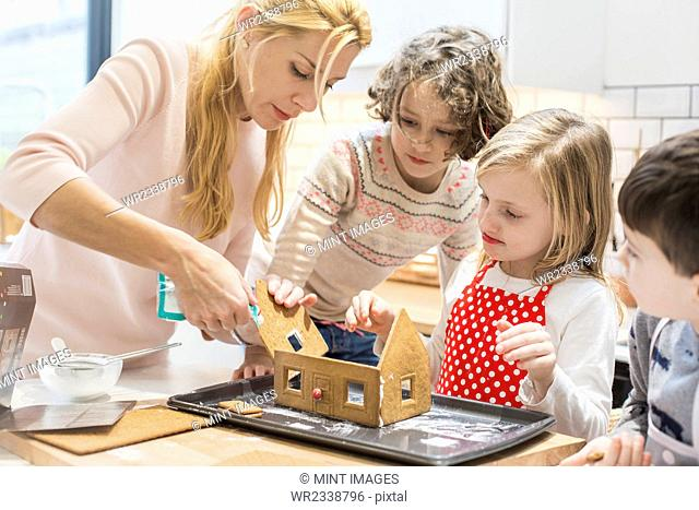 A woman and three children creating a baked gingerbread house