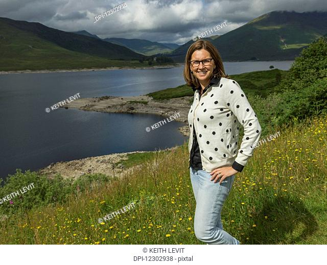 A woman stands on a slope of wildflowers and grass overlooking tranquil water and mountains; Scotland