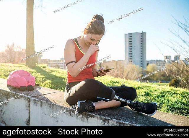 Sporty young woman with leg prosthesis sitting on a wall using cell phone