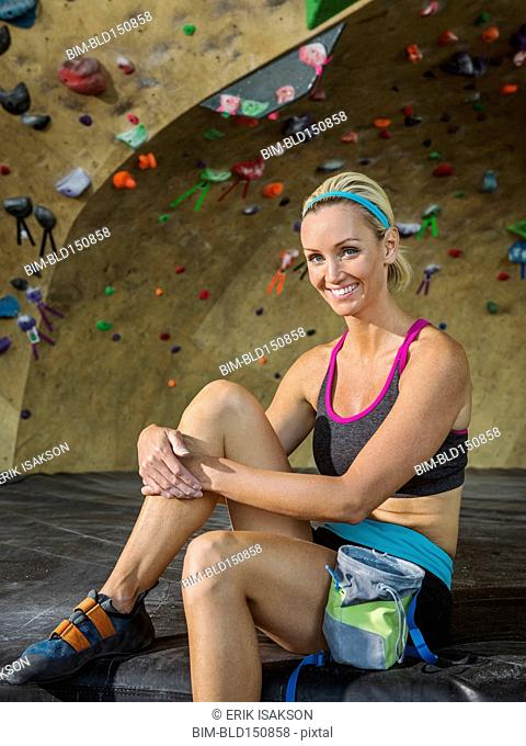 Caucasian woman smiling near indoor rock wall