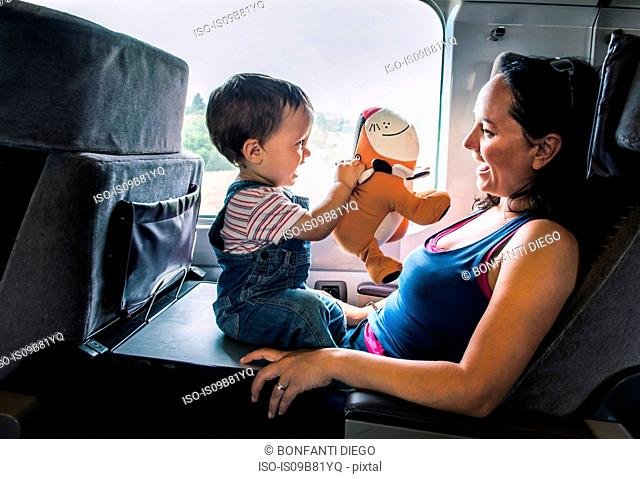 Mother and young son travelling on train, playing together