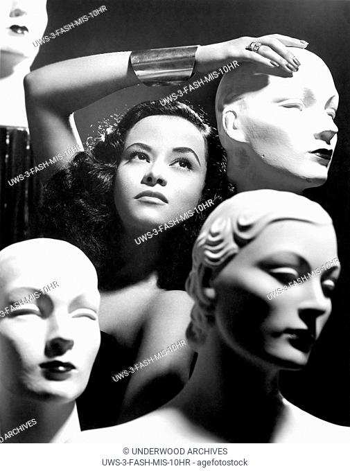 United States: 1952 A woman poses with mannequin heads in a promotional photograph for the Sans-Souci Revue