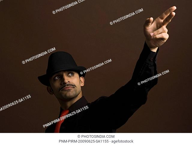 Actor portraying a businessman aiming with his fingers