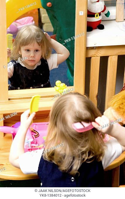 Two Year Old Kid Girl Combing Hair Looking Mirror