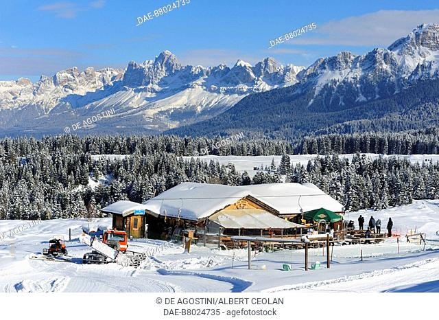 Malga Varena, with the Latemar and the Rosengarten groups in the background, snowy landscape, Lavazejoch pass, Eggental valley, Dolomites, Trentino-Alto Adige