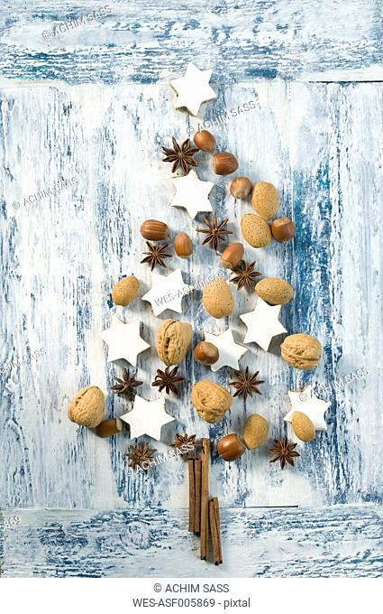 Cinnamon stars, cinnamon sticks, star anise and nuts shaped like a Christmas tree