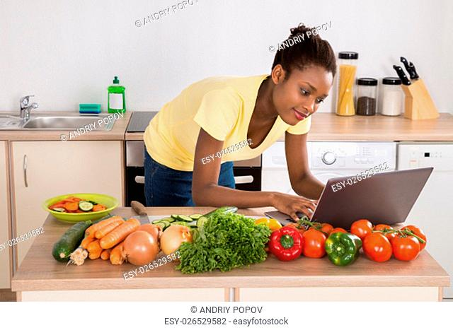 Young African Woman Looking At A Recipe On Laptop In Kitchen