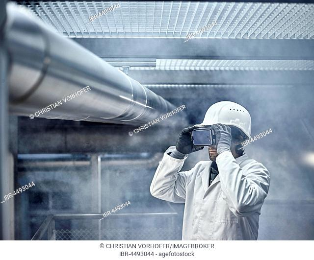 Man with VR goggles, white helmet and lab coat standing in front of industrial plant, Austria